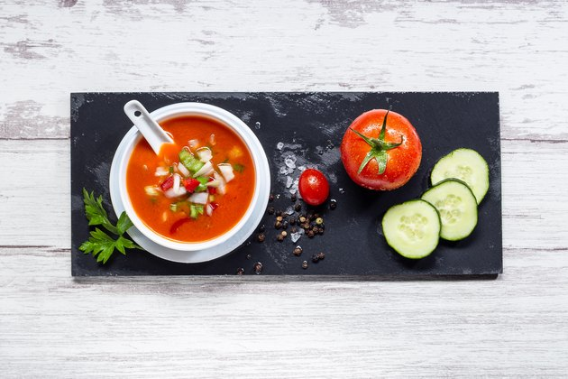 Gazpacho. Traditional Spanish tomato soup with fresh tomatoes, fresh cucumber, on white wood base. Top view