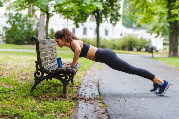 Young woman doing push-ups on the park bench