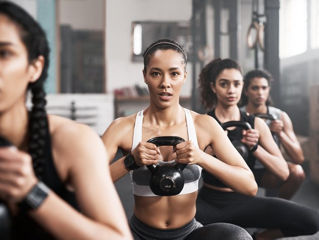 Women in a kettlebell class, trying to avoid making form mistakes