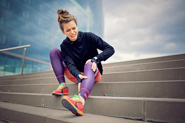Injured runner girl is sitting on the city stairs