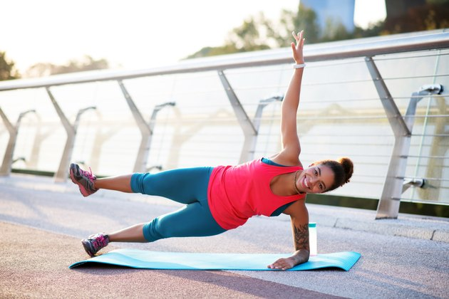 Woman raising her leg while doing side plank