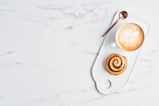 Freshly baked cinnamon roll and coffee with latte art