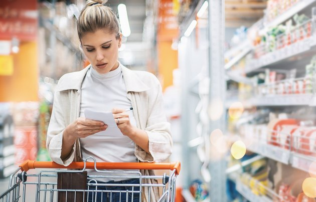 Woman checking her list while shopping in a supermarket