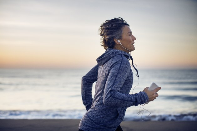 Woman jogging while listening music at beach against sky