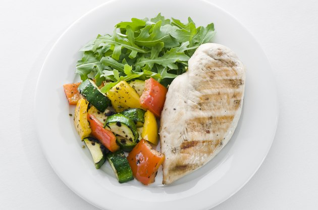 Chicken and roasted veg with lettuce on white plate