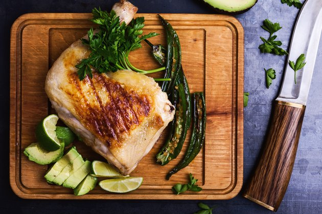 Grilled chicken leg and green vegetables on cutting board