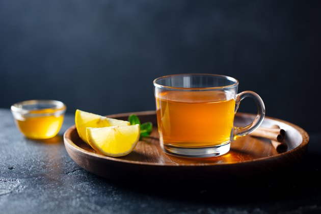 Tea cup with honey and lemon on wooden tray. Grey background. Copy space.