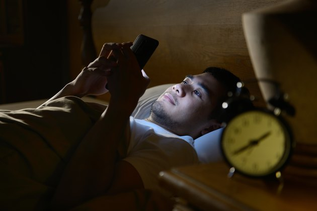Young man with insomnia using a smartphone in his bed late at night