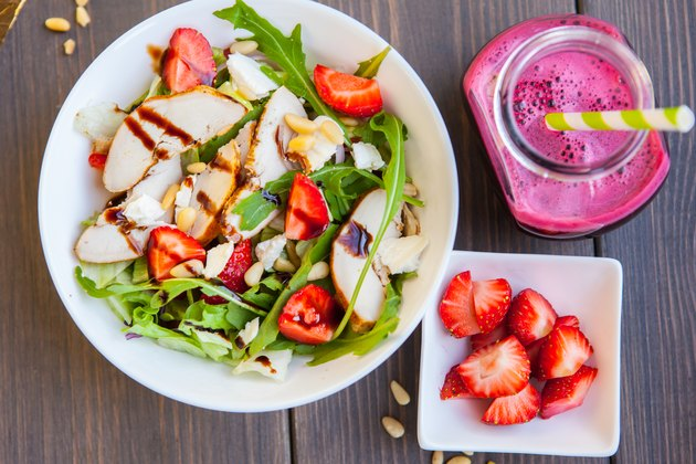 Strawberries salad with pine nuts, arugula and chicken. Beet  fresh juice. Healthy & fitness food. top view