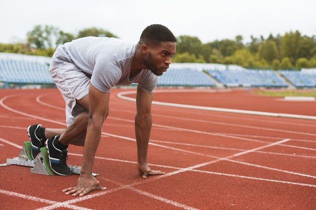 Fit afro-american runner in starting position on stadium