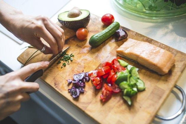 Woman preparing vegetables and salmon on chopping board for Mediterranean diet