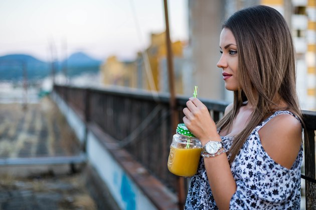 Beautiful woman drinking smoothie on roof
