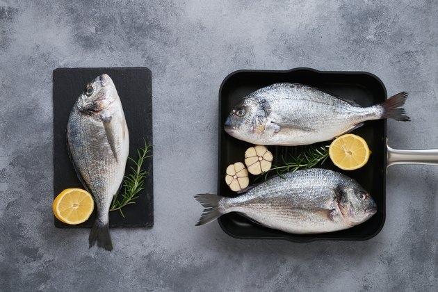 Three Fresh raw sea bream fish (dorado) on gray background. Healthy food concept. Top view, copy space
