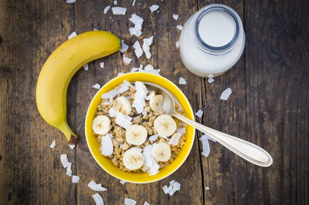 Bowl of granola, banana slices and coconut flakes