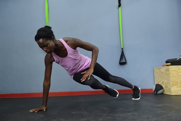 Woman practicing in a gym doing a side plank