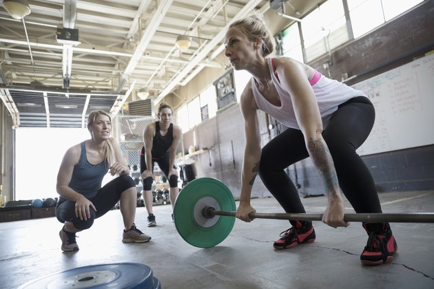 Women motivating friend weightlifting, doing barbell deadlift at gritty gym