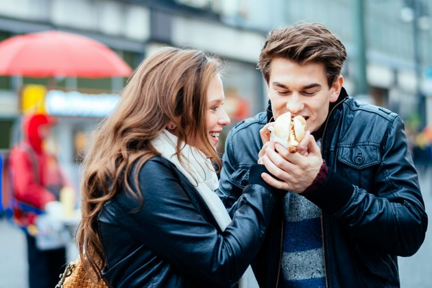 A couple eating a hot dog together