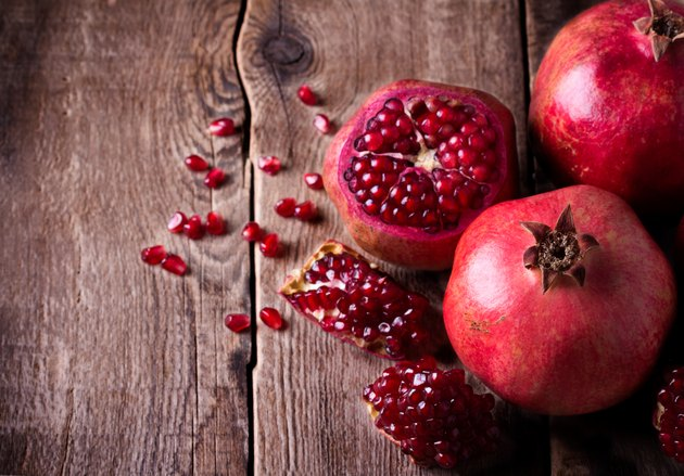 Some red pomegranates on old wooden table