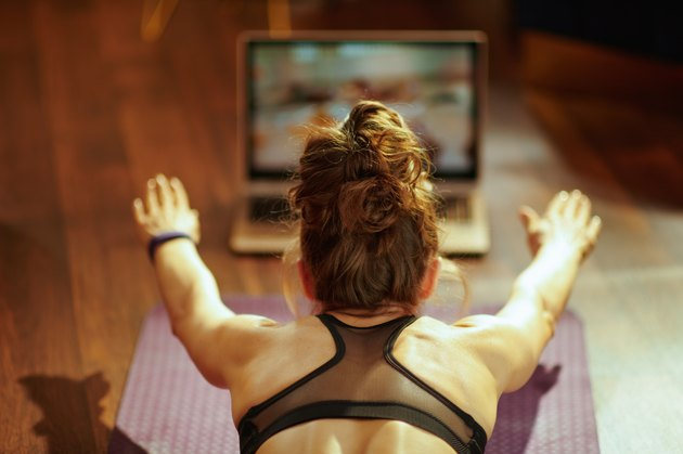 woman playing fitness game on internet while doing her workout