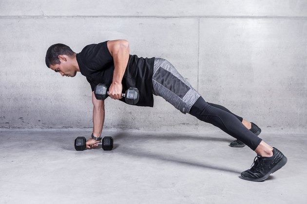 Man doing a renegade row exercise with dumbbells during an upper body workout