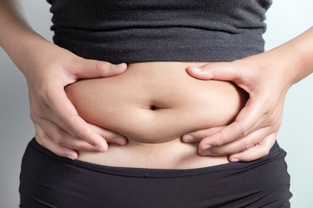 Midsection Of Woman Touching Stomach Against Gray Background