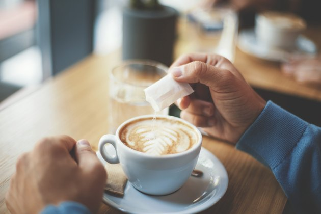 Young man with sensitive stomach puting sugar in his coffee