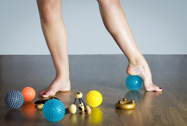 ballet dancer massaging her foot with blue ball for massage