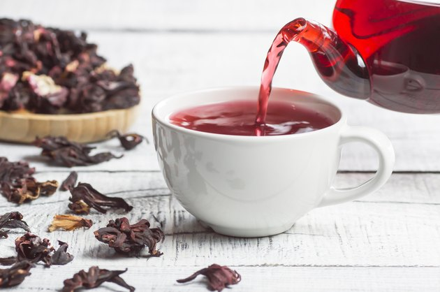 White cup of healthy hibiscus tea pouring from the teapot with dried hibiscus flowers on white wooden background, winter hot drink concept for cold and flu