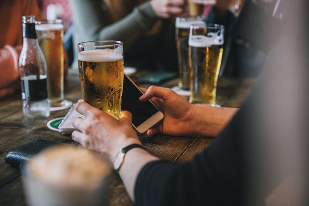 A group of friends drinking pints of beer at a bar