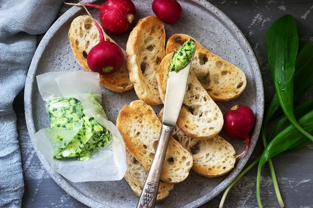 Butter with wild garlic, slices of bread and radish, ingredients for making a sandwich.