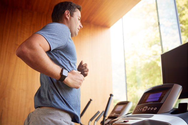 Man Exercising On Treadmill At Home Wearing Smart Watch