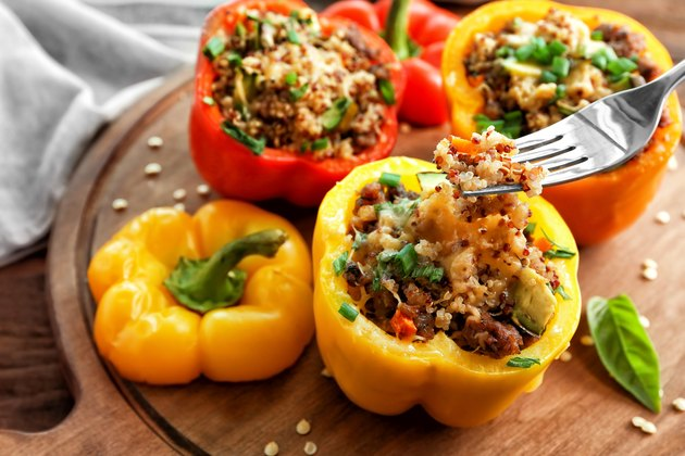 Red, yellow and orange bell peppers stuffed with quinoa, sitting on a wooden board