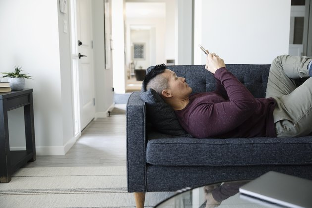 Man relaxing, using smart phone on living room sofa