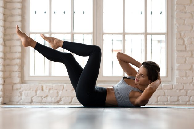 Young sporty woman practicing, doing bicycle crunches pose