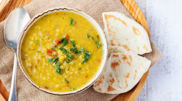 Toor dal with pita bread in a ceramic white bowl on a wooden background. Top view. Copy space