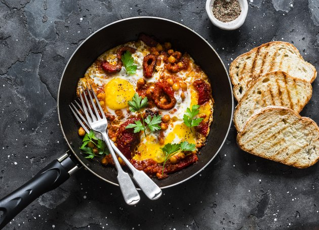 Shakshuka with baked sweet peppers and chickpeas in frying pan on a dark background, top view