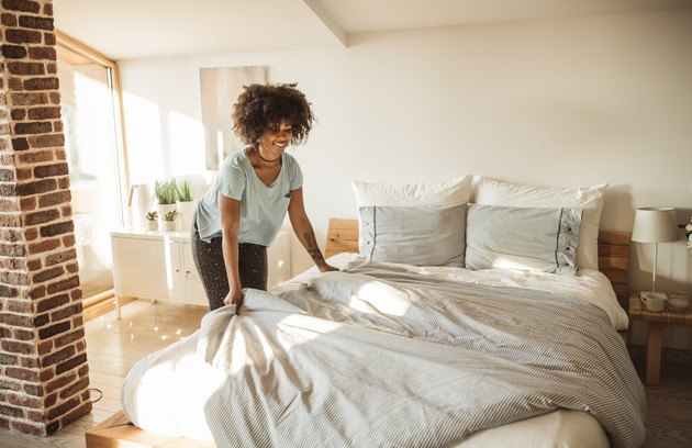 A woman changing the sheets on her bed at home