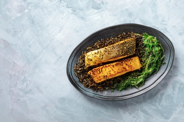 salmon with sesame seeds, wakame and wild black rice, top shot with a place for text