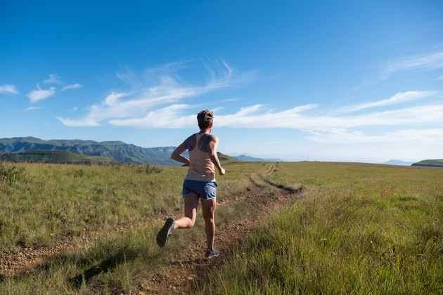 Fit woman running along a mountain path