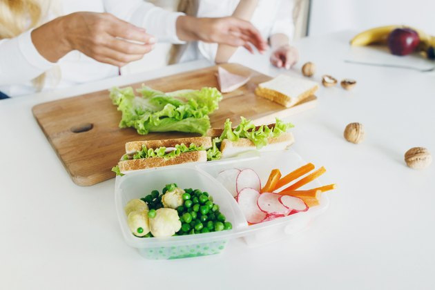 Snack meal prep with sandwich and fresh vegetables, bottle of water on the home kitchen table. In the background, the mother and her daughter are preparing food. Healthy eating concept