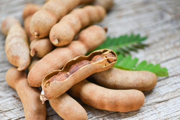 Tamarind and leaves tropical fruit - Sweet tamarind on wooden background