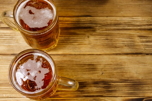 Two mugs of beer on a wooden table. Top view, copy space