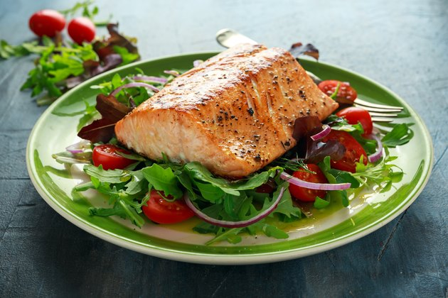 A baked salmon steak with tomato, onion, and leafy green salad on a plate