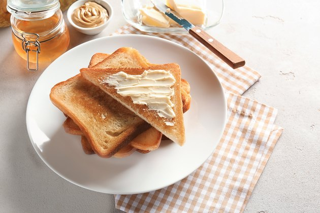 Plate with toasted bread and butter on table