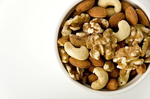 mix of nuts in a cocotte on a white background.