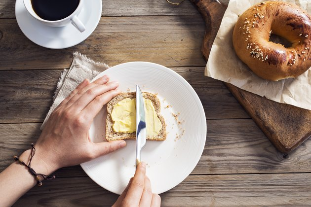 Woman hand spreading vegan butter on sliced bread