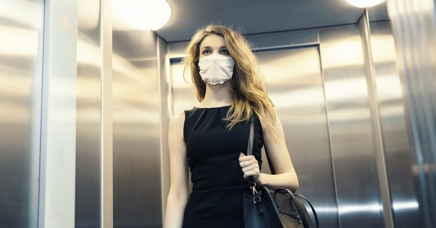 woman wearing face mask in elevator going to work