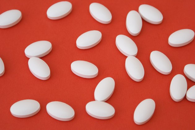White oval IP 466 ibuprofen pills on a red background