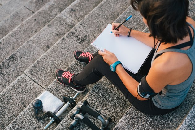 Urban female athlete focusing on her goals writting on notepad