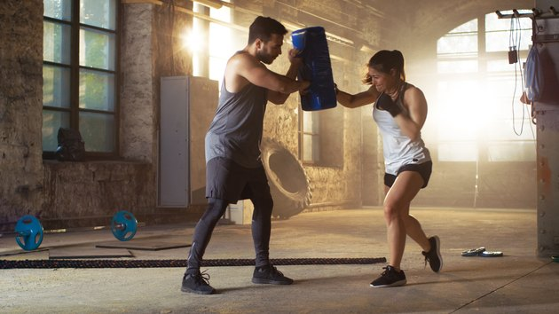 Athletic Woman Hits Punching Bag that Her Partner/ Trainer Holds. She's Professional Fighter and is Training in a Gym.